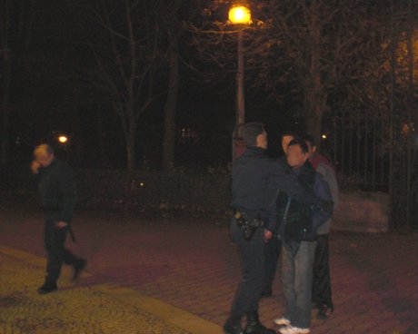 Police ist arresting two migrants in a park.