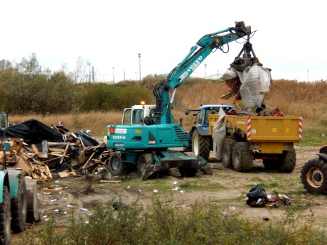 Crane is used to put the remains of the destroyed houses in a lorry.