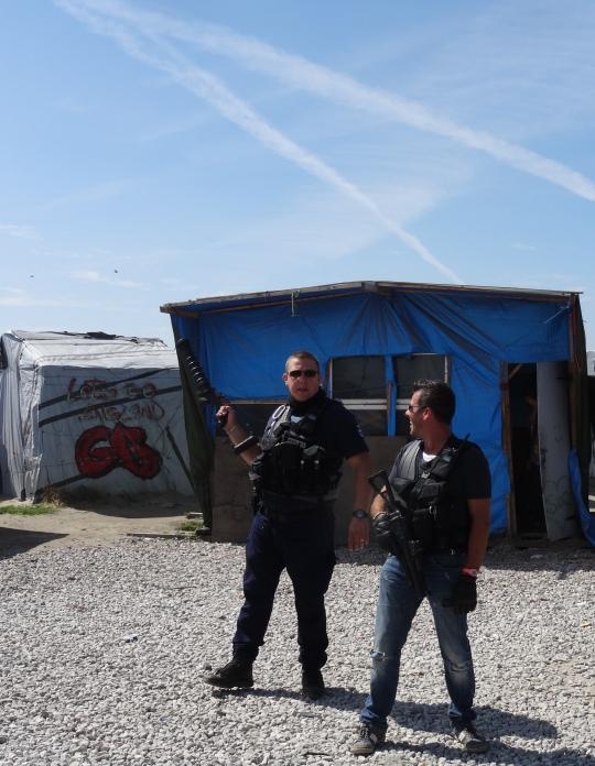 Deux hommes prenant tranquillement le soleil, comme si de rien n'était le lance-grenade lacrymogène à la main.