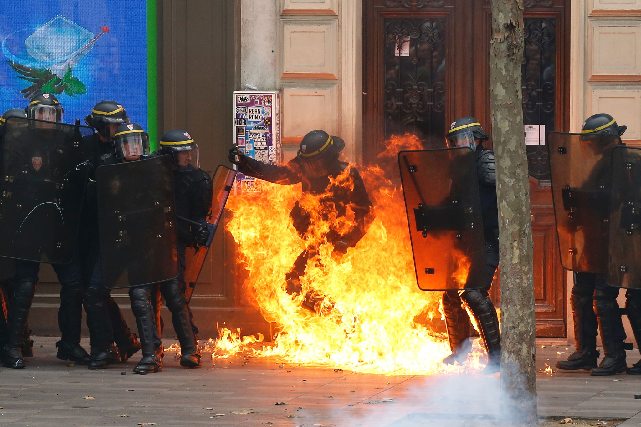 A French riot police officer gesturea as he is surrounded by flames, during a demonstration against the controversial labour reforms of the French government in Paris on September 15, 2016. Opponents of France's controversial labour reforms took to the streets on September 15, 2016 for the 14th time in six months in a last-ditch bid to quash the measures that lost the Socialist government crucial support on the left. Scores of flights in and out of France were cancelled as air traffic controllers went on strike to try to force the government to repeal the changes that became law in July. / AFP PHOTO / Thomas SAMSONTHOMAS SAMSON/AFP/Getty Images